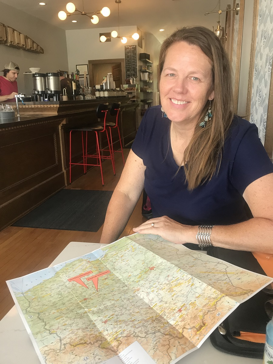 A woman holds a map of the location of her ancestor's home country.