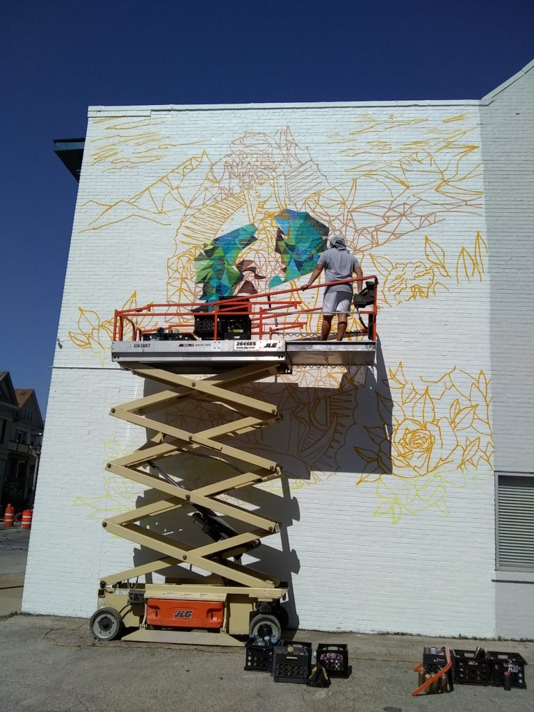 depicts artists working on mural