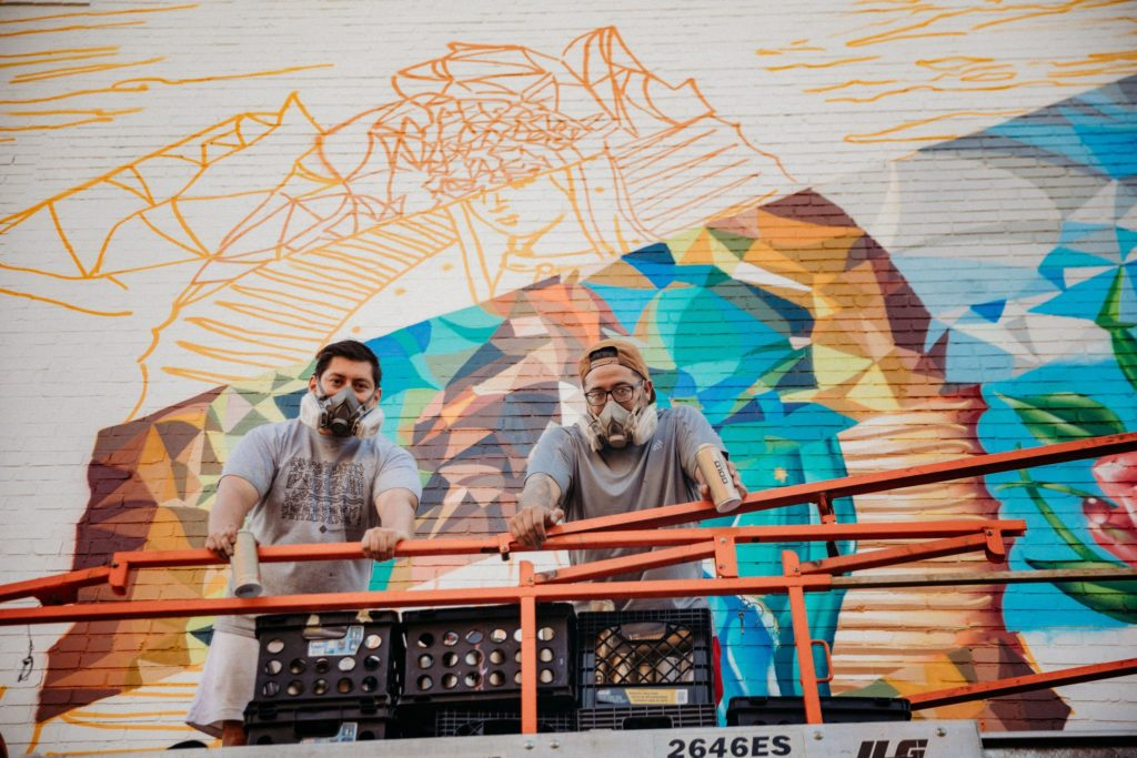 image shows two artists who painted the mural behind them